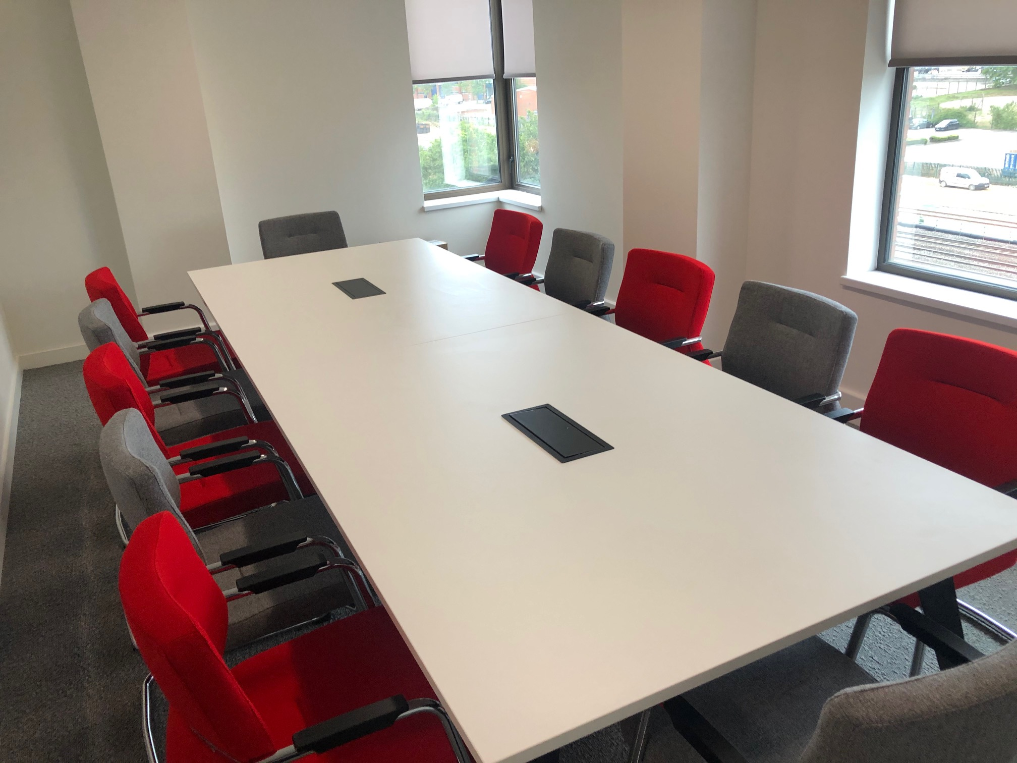 office meeting desk with red and grey chairs